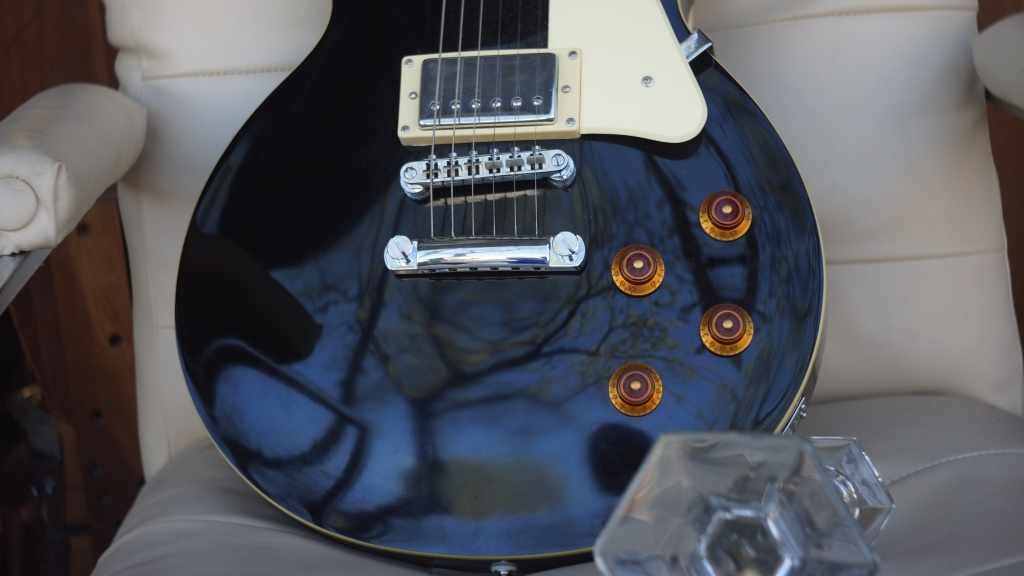 This was taken at f/3.5. Nice colors and resolution of this guitar in a thrift shop.